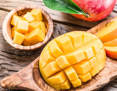 マンゴーの果実と木製のテーブル上のマンゴーのキューブ。 写真素材
