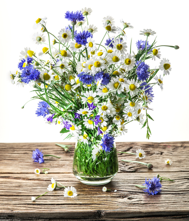 flowers in vase: Bouquet of chamomiles and cornflowers in the vase on the wooden table. White background.