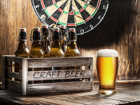 Crafting beer in bottles and glasses. On a wooden wall hangs game of darts. Stock Photo