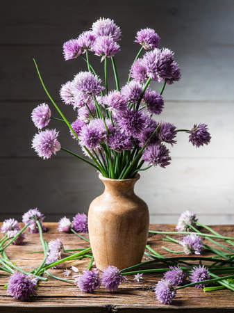 Bouquet of onion (chives) flowers in the vase on the wooden table.