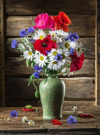 flowers in vase: Bouquet of field flowers in the vase on the wooden table.