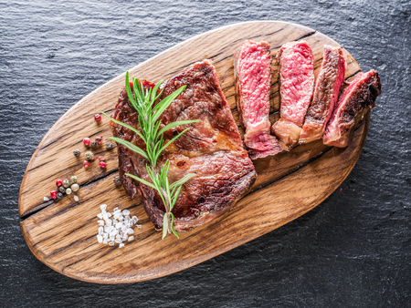fillets: Medium Ribeye steak with spices on the wooden tray. Stock Photo