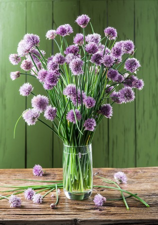 decoracion mesas: Bouquet of onion (chives) flowers in the vase on the wooden table.
