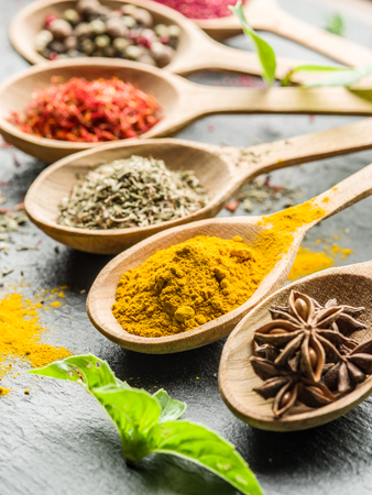 spicy cooking: Assortment of colorful spices in the wooden spoons. Stock Photo
