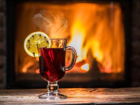 オレンジ スライス、クローブ、シナモンスティック ホットホット ワイン。背景に暖かい暖炉と暖炉。