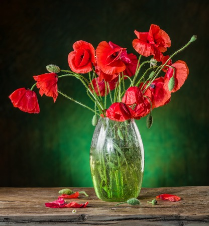red flower: Bouquet of poppy flowers in the vase on the wooden table.
