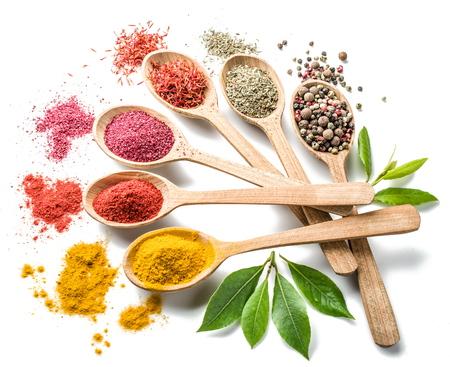 Assortiment van kleurrijke kruiden in de houten lepels op de witte achtergrond. Stockfoto