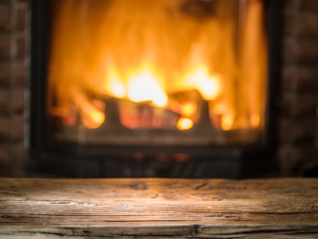 fire wood heat: Old wooden table and fireplace with warm fire on the background.