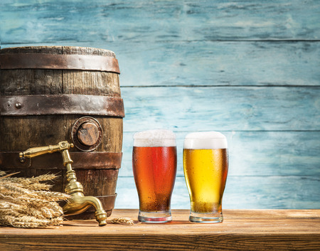 ale: Glasses of  beer and ale barrel on the wooden table. Craft brewery.