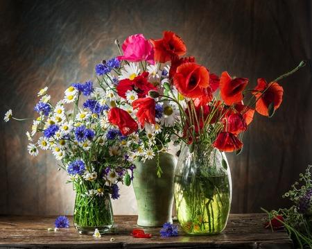 campo de flores: Ramo de flores de campo en el florero sobre la mesa de madera. Foto de archivo