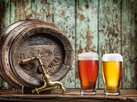 microbrewery: Glasses of  beer and ale barrel on the wooden table. Craft brewery.