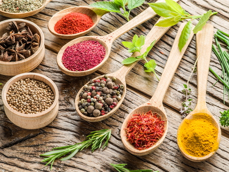peppercorn: Assortment of colorful spices in the wooden spoons on the wooden table. Stock Photo