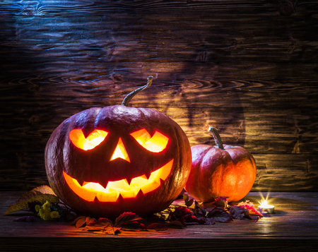 attribute: Grinning pumpkin lantern or jack-o-lantern is one of the symbols of Halloween. Halloween attribute. Wooden background. Stock Photo