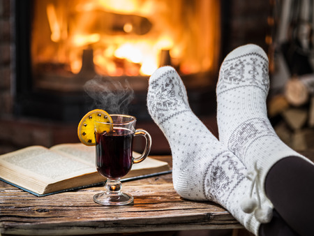 Warming and relaxing near fireplace. Woman feet near the cup of hot wine in front of fire. Foto de archivo