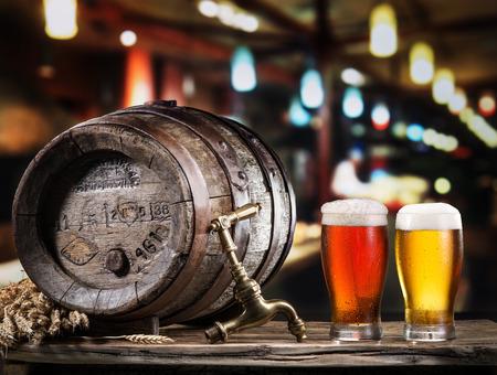 vasos de cerveza: Vasos de cerveza y cerveza de barril en la mesa de madera. cervecería artesanal. Foto de archivo