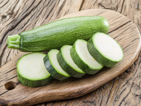 Zucchini with slices on a wooden table. Standard-Bild
