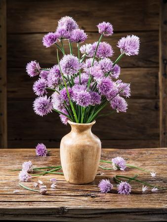 decoracion mesas: Ramo de cebolla (cebollino) flores en el florero sobre la mesa de madera.