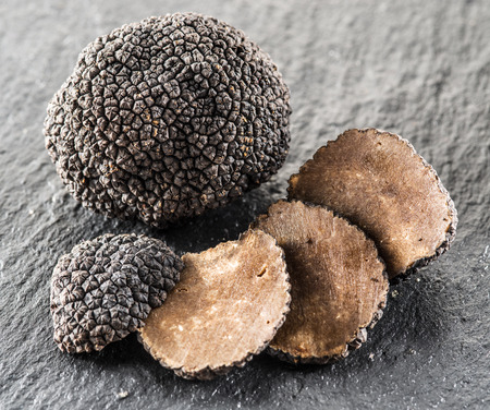 Black truffles and truffle slices on the graphite board. Stok Fotoğraf