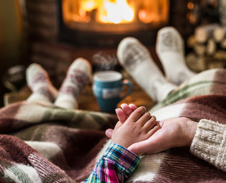 Warming and relaxing near fireplace. Mother and daughter holding hands in front of fire. Stock Photo