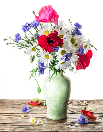 flowers in vase: Bouquet of field flowers in the vase on the wooden table. White background. Stock Photo