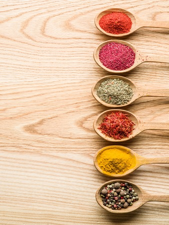 spicy cooking: Assortment of colorful spices in the wooden spoons on the wooden table. Stock Photo