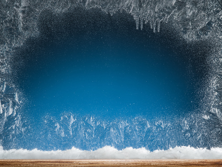 Wooden sill and frozen window. Christmas or New Year background. Stock Photo