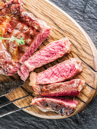 the medium: Medium Ribeye steak on the wooden tray. Stock Photo