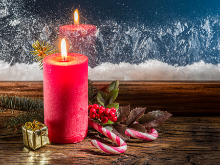 christmas candle: Christmas candle, fir branch, candy canes and frozen window on background. Stock Photo