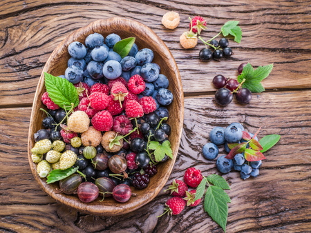 Ripe berries in the wooden bowl on the table. Stock Photo