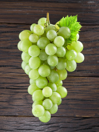white grape: Bunch of white grapes. Old wood on the background. Stock Photo