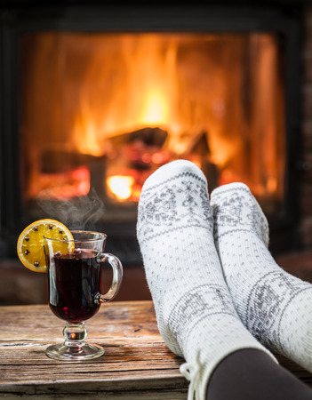 vin chaud: Warming and relaxing near fireplace. Woman feet near the cup of hot wine in front of fire. Banque d'images