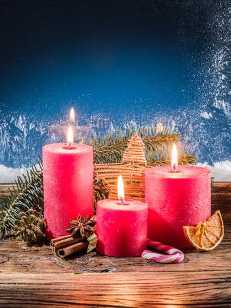 Cristmas: Cristmas candle lights and frozen window. Christmas background. Stock Photo