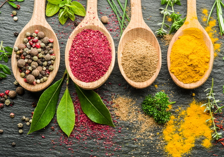 peppercorn: Assortment of colorful spices in the wooden spoons. Stock Photo
