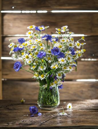 decoracion mesas: Ramo de manzanillas y acianos en el florero sobre la mesa de madera. Foto de archivo