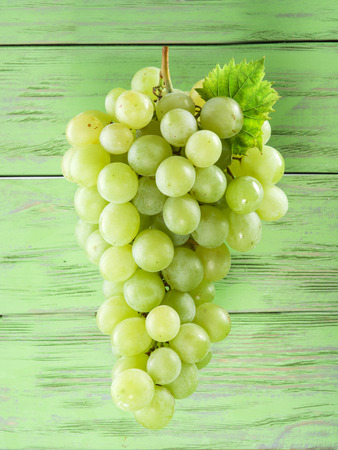 vinery: Bunch of white grapes. Old wood on the background. Stock Photo