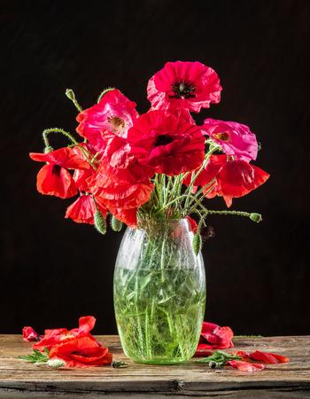 decoracion mesas: Ramo de flores de amapola en el florero sobre la mesa de madera. Foto de archivo