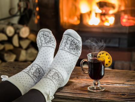 vin chaud: Le réchauffement et près de cheminée relaxant. Femme pieds près de la coupe de vin chaud devant le feu. Banque d'images