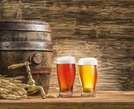 condensed: Glasses of  beer and ale barrel on the wooden table. Craft brewery.