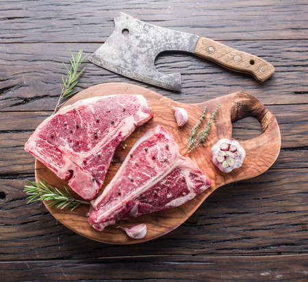 tbone: Steak T-bone with spices on the wooden cutting board. Stock Photo