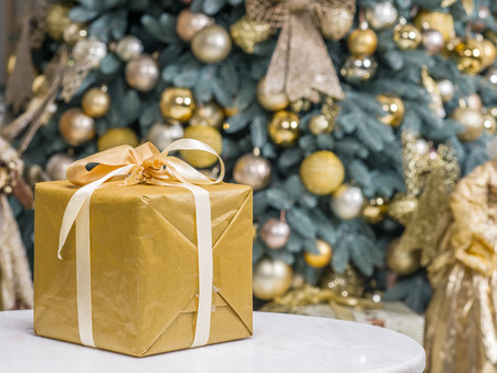 come home: Yellow gift box and decorated New Year Tree on the background.