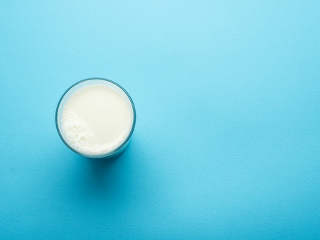 Glass of milk on the blue background. Top view.