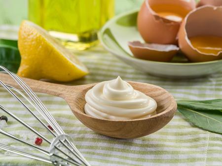 salsa mayonesa Natural en la cuchara de madera y su ingrediente en el fondo.