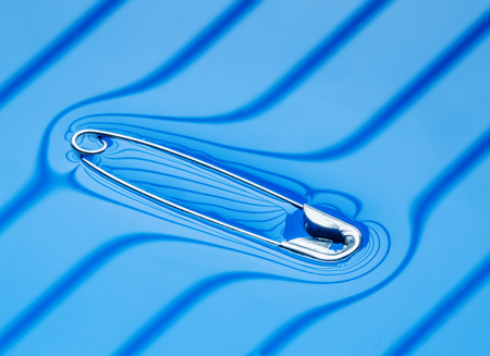 surface tension: Physical experiment - pin floating on water surface.