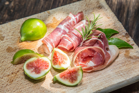 Ripe fig fruits and bacon or prosciutto. Food to accompany the drinks. Stock Photo