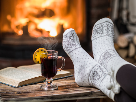 Warming and relaxing near fireplace. Woman feet near the cup of hot wine in front of fire. Stock Photo