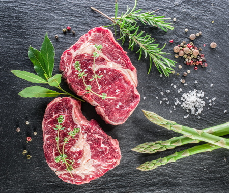 Rib eye steaks with spices on the black background.  Stock Photo