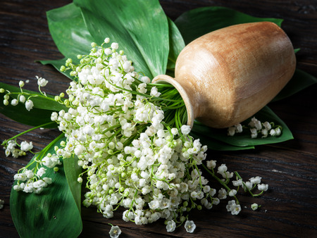 sweetly: Lily of the valley bouquet on the wooden table.