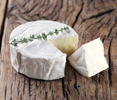 Camembert cheese on old wooden table.