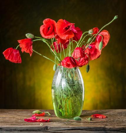 ramo de flores: Ramo de flores de amapola en el florero sobre la mesa de madera. Foto de archivo