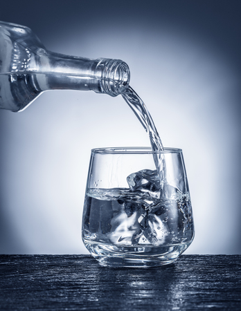 Pouring alcohol into a glass. Monochrome picture. Stock Photo